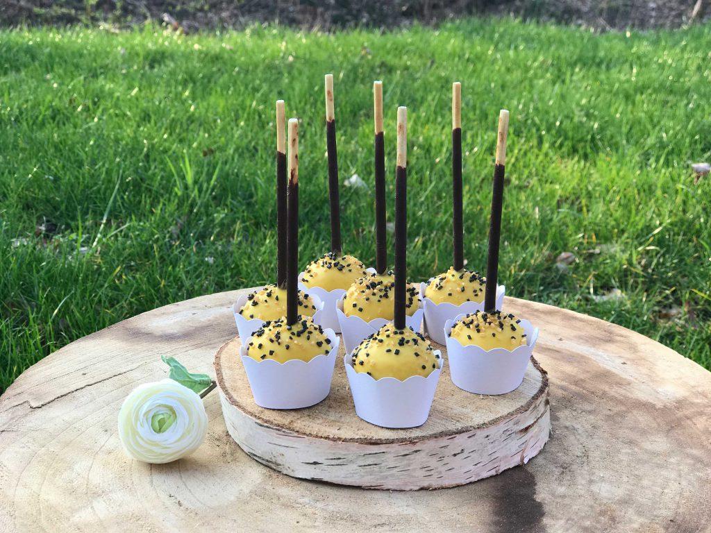 Cake Pops in gelb mit Schoko Streuseln, fotografiert draußen auf einer Baumscheibe