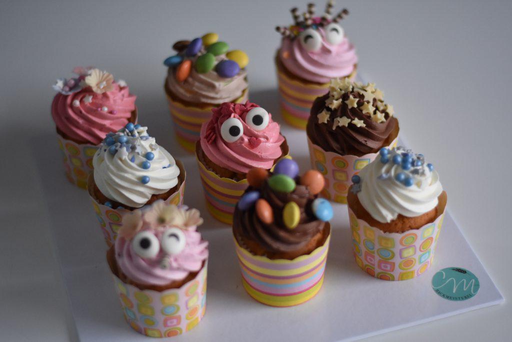 Kinder Cup Cakes dekoriert mit Schokolinsen in bunten Förmchen