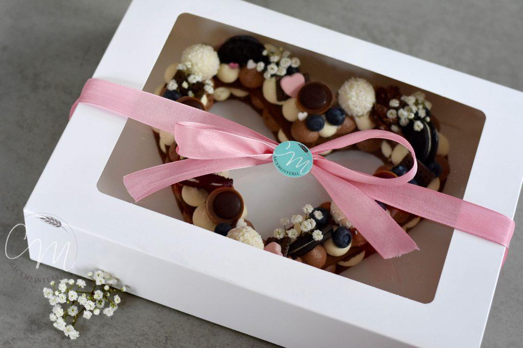 Herzkuchen eingepackt in weiße Box mit Klarsichtfenster.