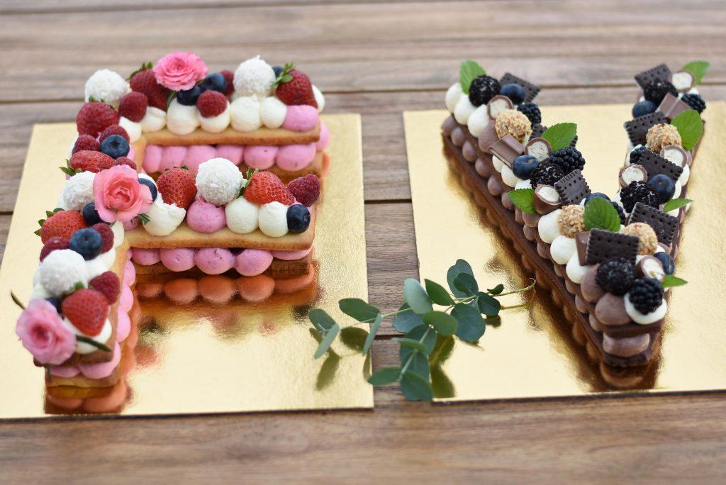Zwei Buchstabenkuchen. Einer mit Beeren dekoriert, einer mit Schokolade